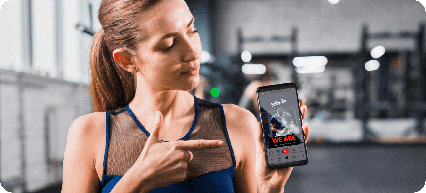 Image of a girl pointing to a mobile with the Holiday Gym application