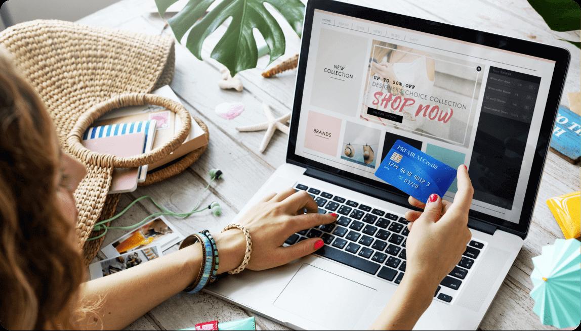 Imagen de una chica comprando con su ordenador en una tienda online con una tarjeta en la mano